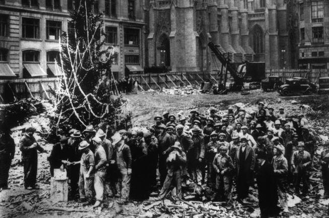 Robotnicy budowlani stojący obok pierwszej świątecznej choinki w Rockefeller Center w 1931 r, czekający na wypłatę.
